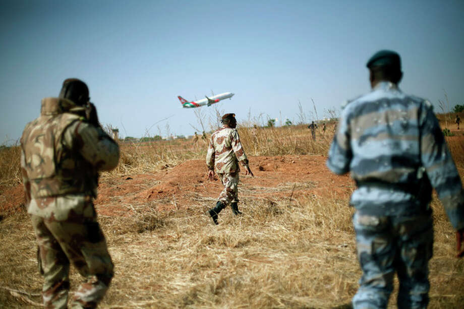 "Mali National Guard soldiers stand guard on the military side of Bamako's airport Wednesday Jan. 16, 2013, as a commercial jet takes off during a joined visit to French and Malian troops by Mali's President Dioncounda Traore and French Ambassador to Mali Christian Rouyer. French troops pressed northward in Mali toward territory occupied by radical Islamists on Wednesday, military officials said, announcing the start of a land assault that will put soldiers in direct combat ""within hours.""(AP Photo/Jerome Delay) / AP"