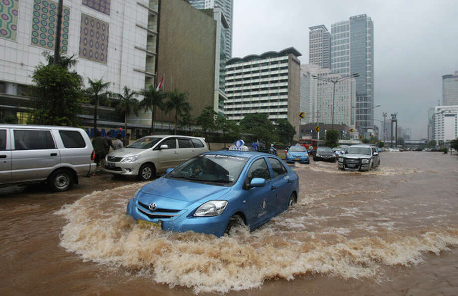 A taxi wades through a flooded street in Jakarta, Indonesia Friday, Jan. 18, 2013. Indonesia's army deployed rubber boats in the capital's business district on Thursday to rescue people trapped in floods that inundated much of the city of 14 million people.(AP Photo/Achmad Ibrahim) / AP