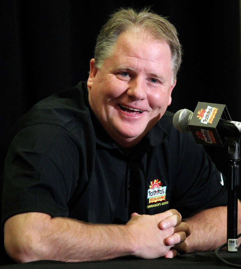 FILE - In this Jan. 3, 2013 file photo, Oregon head coach Chip Kelly laughs as he answers a reporter's question during media day for the Fiesta Bowl NCAA college football game in Scottsdale, Ariz. The Philadelphia Eagles have hired Kelly after he originally chose to stay at Oregon. Kelly becomes the 21st coach in team history and replaces Andy Reid, who was fired on Dec. 31 after a 4-12 season. (AP Photo/Paul Connors, File) / FR5880 AP