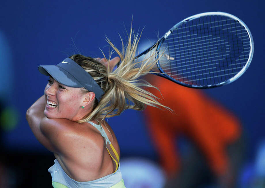 Russia's Maria Sharapova hits a return to Japan's Misaki Doi during their second round match at the Australian Open tennis championship in Melbourne, Australia, Wednesday, Jan. 16, 2013. (AP Photo/Rob Griffith) / AP