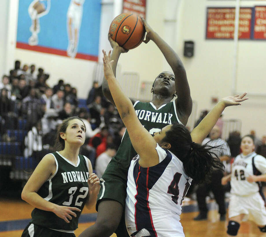 Hour photo/John NashNorwalk's Emma Oyomba, center, puts up a shot over Brien McMahon's Kiara Velez as Norwalk's Alex Weber looks on during Friday's city showdown at King-Kehoe Gym on the McMahon campus. Oyomba led the Bears to a 44-39 victory.