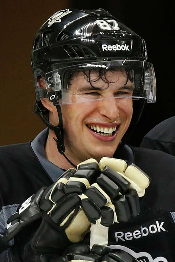 In this photo taken Jan. 14, 2013, Pittsburgh Penguins captain Sidney Crosby smiles during NHL hockey practice at the Consol Energy Center in Pittsburgh. The headaches are gone. Finally. So are the doubts, the ones Crosby couldn't outrun as he rehabilitated from concussion-like symptoms that robbed hockey's best player from two years in the middle of his prime. (AP Photo/Gene J. Puskar) / AP