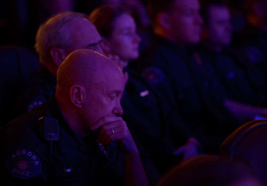 Aurora Police Officer Mike Hawkins, a 18 year veteran and first responder to the shooting sits with other Aurora Police officers during the reopening and remembrance ceremony at the Century Aurora cinema, formerly the Century 16, Thursday, Jan. 17, 2013 in Aurora, Colo. The cinema is where 12 people were killed and dozens injured in a shooting rampage last July. (AP Photo/The Denver Post, RJ Sangosti, Pool) / Pool Denver Post