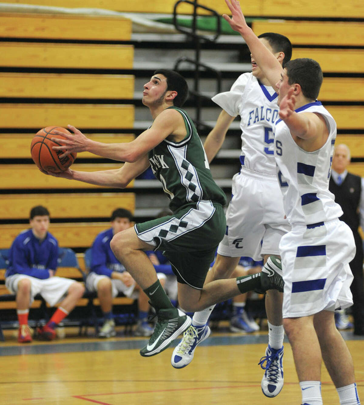 Hour photo/John Nash Norwalk's Nick Bocanfuso, left, drives between Fairfield Ludlowe's Matt Doyle (5) and Stephan Scholz (right) during the first quarter of Friday's game in Fairfield. Bocanfuso scored all 10 of his points in the first quarter to lead Norwalk to a 58-53 win.