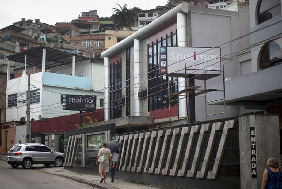 """People walk along the sidewalk past the Shalimar Hotel, known as a love hotel in Rio de Janeiro, Brazil, Thursday, Jan. 17, 2013. Like about a third of city's 180 hotels that rent rooms by the hour, mostly for amorous rendezvous, the Shalimar is trading its oversized beds and bondage-ready chairs for proper couches, functional desks and other business-friendly furnishings. The goal is reinvention as a standard pay-by-the-day tourist hotel, after the government slashed property taxes for love hotels, known as """"motels"""" in Portuguese, that agree to tone down the decor and free up 90 percent of their rooms for the tsunami of visitors expected to flood the city for the 2014 World Cup soccer tournament and the 2016 Olympic Games. (AP Photo/Felipe Dana) / AP"""