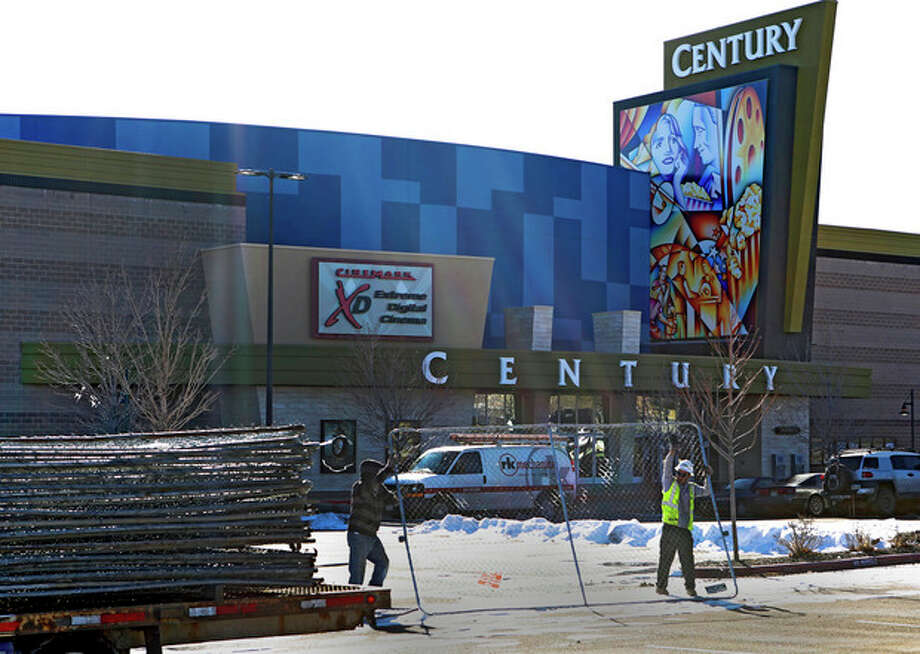 "Workers with American Fence remove the fence from around the Century theater in Aurora, Colo., on Thursday, Jan. 17, 2013. The Colorado movie theater where a gunman killed 12 people and wounded dozens of others reopens Thursday with a private ceremony for victims, first responders and officials. Theater owner Cinemark plans to temporarily reopen the entire 16-screen complex in Aurora to the public on Friday, then permanently on Jan. 25. Aurora's mayor, Steve Hogan, has said residents overwhelmingly support reclaiming what he calls ""an important venue for Aurora."" (AP Photo/Ed Andrieski) / AP"