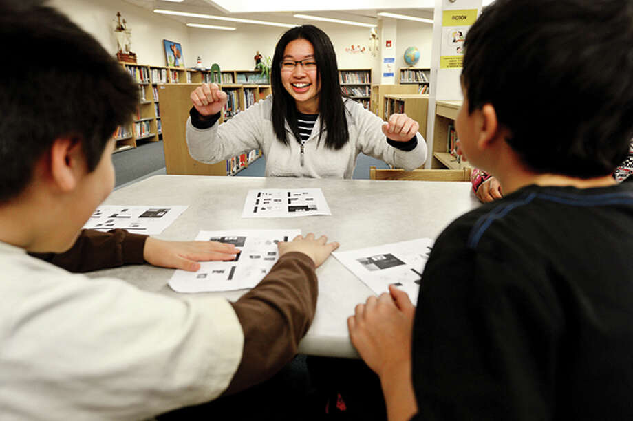 Brien McMahon High School Center for Global Studies students including Vivian Tang teach Chinese and Chinese culture to Brookside students Friday. Hour photo / Erik Trautmann / (C)2012, The Hour Newspapers, all rights reserved