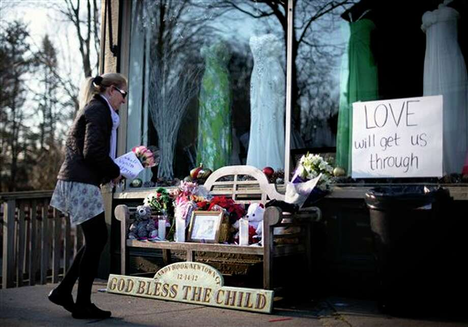 Kerry O'Mahony, of Danbury, Conn., brings a bouquet of flowers to a memorial for the Sandy Hook Elementary School shooting victims down the street from the school's entrance, Wednesday, Dec. 19, 2012, in Newtown, Conn. Newtown has begun returning its students to their classrooms for the first time since last week's massacre and continues the agonizing task of laying others to rest, as this grief-stricken town wrestles with the same questions gripping the country about violence, gun control and finding a way forward. Adam Lanza walked into Sandy Hook Elementary School in Newtown, Dec. 14, and opened fire, killing 26 people, including 20 children, before killing himself. (AP Photo/David Goldman) / AP2012