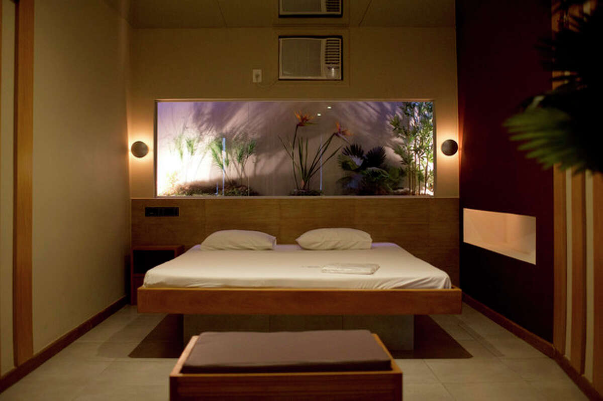 """A newly remodeled room is seen at the Shalimar Hotel, known as a love hotel in Rio de Janeiro, Brazil, Thursday, Jan. 17, 2013. Like about a third of city?'s 180 hotels that rent rooms by the hour, mostly for amorous rendezvous, the Shalimar is trading its oversized beds and bondage-ready chairs for proper couches, functional desks and other business-friendly furnishings. The goal is reinvention as a standard pay-by-the-day tourist hotel, after the government slashed property taxes for love hotels, known as ?""""motels?"""" in Portuguese, that agree to tone down the decor and free up 90 percent of their rooms for the tsunami of visitors expected to flood the city for the 2014 World Cup soccer tournament and the 2016 Olympic Games. (AP Photo/Felipe Dana)"""