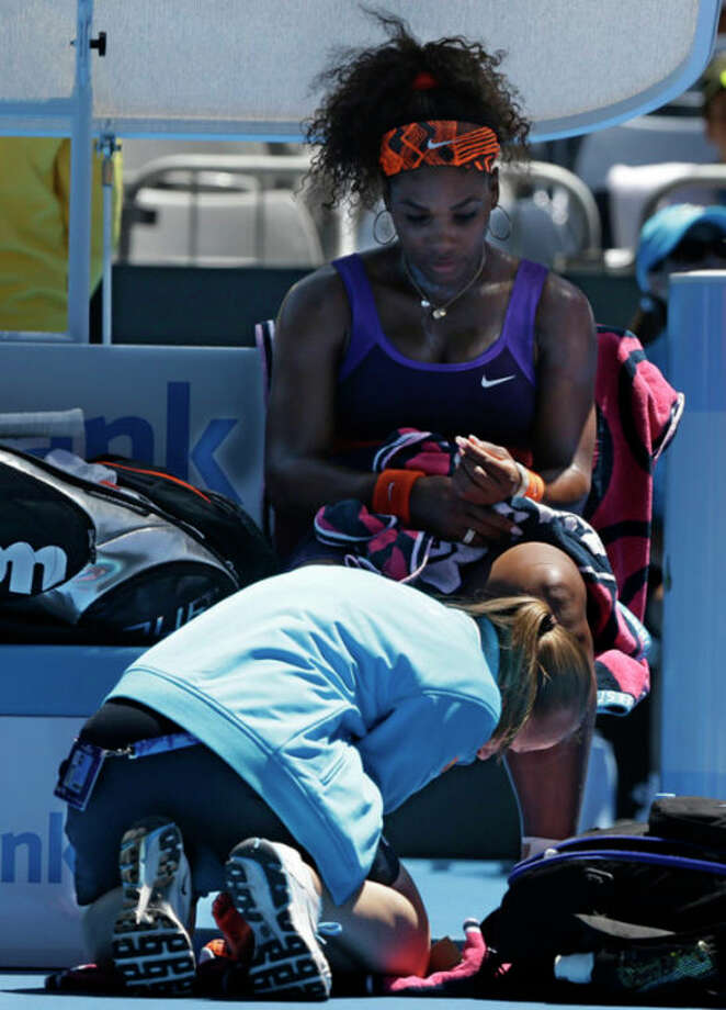 Serena Williams of the US is attended to by a trainer after falling during her first round match against Romania's Edina Gallovits-Hall at the Australian Open tennis championship in Melbourne, Australia, Tuesday, Jan. 15, 2013. (AP Photo/Rob Griffith) / AP