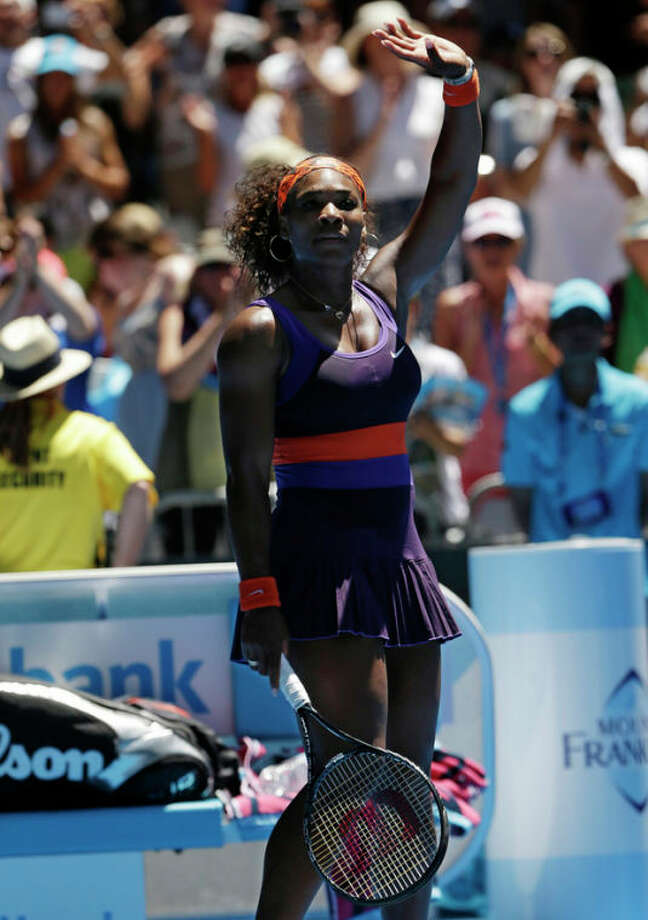 Serena Williams of the US waves to the crowd following her first round win over Romania's Edina Gallovits-Hall at the Australian Open tennis championship in Melbourne, Australia, Tuesday, Jan. 15, 2013. (AP Photo/Rob Griffith) / AP
