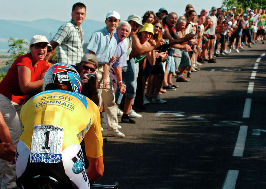 FILE - In this July 23, 2005, file photo spectators urge on overall leader Lance Armstrong, left, during the 20th stage of the Tour de France cycling race in Saint-Etienne, France. After a decade of denial and being stripped of his titles, Armstrong has finally come clean_ During an interview with Oprah Winfrey taped Monday, Jan. 14, 2013, Armstrong said he used performance-enhancing drugs to win the Tour de France, a person familiar with the situation told The Associated Press. (AP Photo/Bernard Papon, Pool, File) / Pool L'EQUIPE