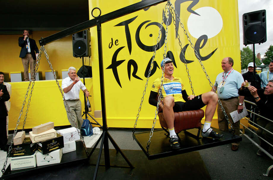 FILE - In this July 7, 2005, file photo, Lance Armstrong laughs as he has his weight matched with boxes containing champagne bottles while seated on a scale before the sixth stage of the Tour de France cycling race between Troyes and Nancy, eastern France. In 2012 Armstrong was stripped of his Tour de France titles, lost most of his endorsements and was forced to leave the Livestrong foundation last year after the U.S. Anti-Doping Agency issued a damning, 1,000-page report that accused him of masterminding a long-running doping scheme. (AP Photo/Christophe Ena, File) / AP