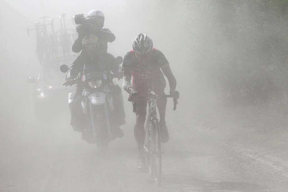 FILE - In this July 6, 2010, file photo, Lance Armstrong rides in a cloud of dust on a cobblestone section during the third stage of the Tour de France cycling race over 213 kilometers (132.4 miles) with start in Wanze, Belgium, and finish in Arenberg, France. Armstrong is said to be worth around $100 million_but most sponsors dropped him after USADA's scathing report _ at the cost of tens of millions of dollars _ and soon after, he left the board of Livestrong. (AP Photo/Fred Mons, Pool, File) / Pool L'EQUIPE
