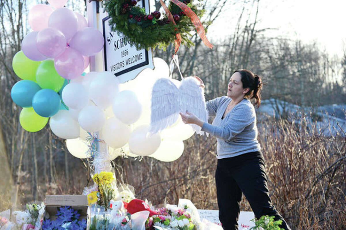 Visitors and residents mourn the tragedy in Newtown Saturday afternoon by putting out signs and leaving gifts at a makeshift memorial outside the school. Hour photo / Erik Trautmann