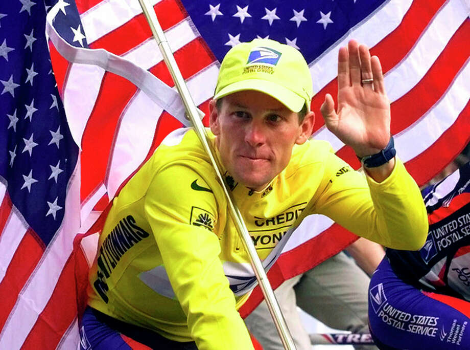FILE - In this July 23, 2000, file photo, winner Lance Armstrong rides down the Champs Elysees after the final stage of the Tour de France cycling race in Paris. Armstrong also won the Prince of Asturias Award in Sports in 2000. Armstrong was stripped of his seven Tour de France titles and banned for life by cycling's governing body following a report from the U.S. Anti-Doping Agency that accused him of leading a massive doping program on his teams. (AP Photo/Laurent Rebours, File) / AP