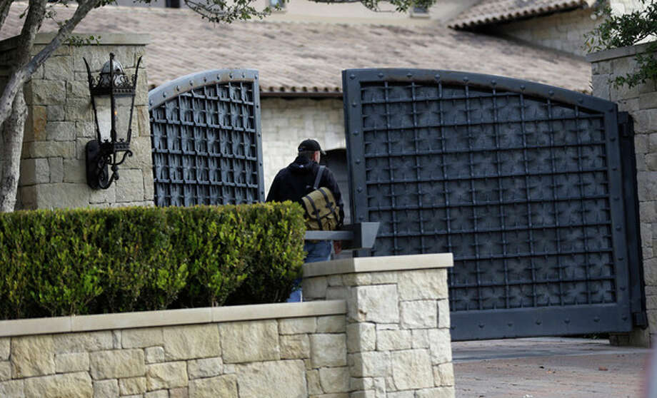 "An unidentified man enters a gate at the home of cyclist Lance Armstrong, Monday, Jan. 14, 2013, in Austin, Texas. After more than a decade of denying that he doped to win the Tour de France seven times, Armstrong was set to sit down Monday for what has been trumpeted as a ""no-holds barred,"" 90-minute, question-and-answer session with Oprah Winfrey. (AP Photo/Eric Gay) / AP"