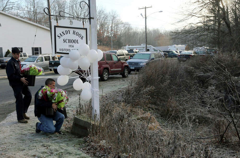 A couple of volunteer firefighters place flowers at a makeshift memorial at a sign for the Sandy Hook Elementary school, Saturday, Dec. 15, 2012 in Sandy Hook village of Newtown, Conn. The massacre of 26 children and adults at Sandy Hook Elementary school elicited horror and soul-searching around the world even as it raised more basic questions about why the gunman, 20-year-old Adam Lanza, would have been driven to such a crime and how he chose his victims. (AP Photo/Mary Altaffer) / AP