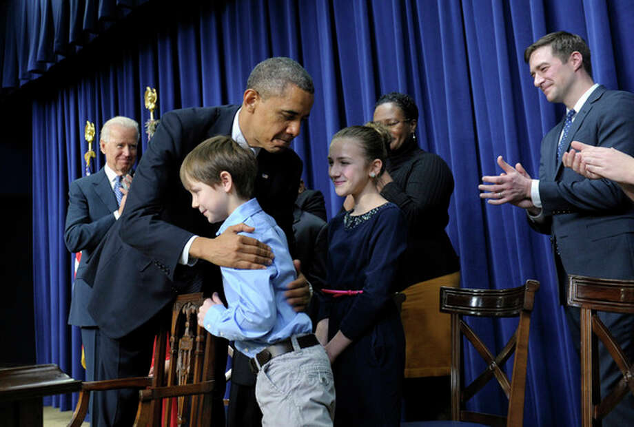 President Barack Obama, accompanied by Vice President Joe Biden, left, hugs eight-year-old letter writer Grant Fritz during a news conference on proposals to reduce gun violence, Wednesday, Jan. 16, 2013, in the South Court Auditorium at the White House in Washington. Obama and Biden were joined by law enforcement officials, lawmakers and children who wrote the president about gun violence following the shooting at an elementary school in Newtown, Conn., last month. (AP Photo/Susan Walsh) / AP
