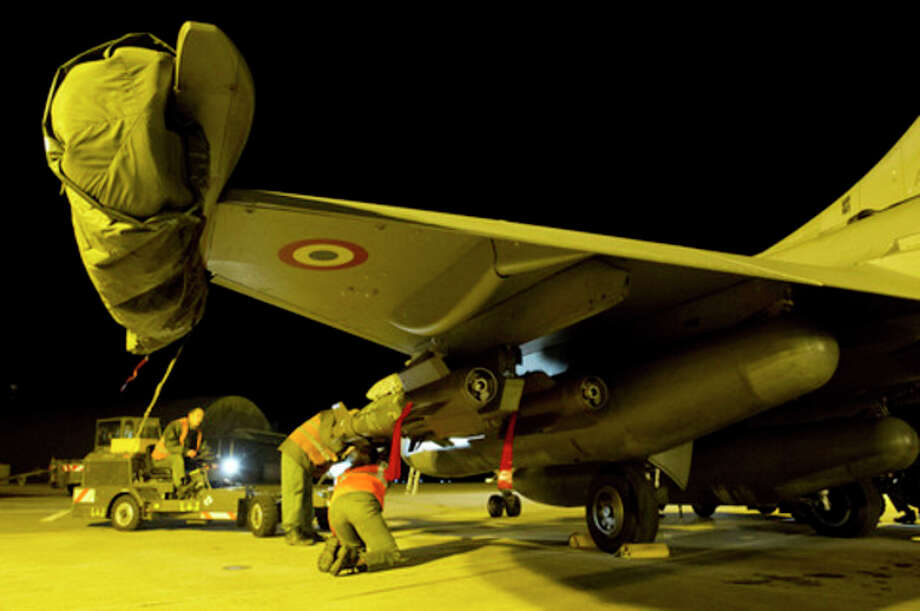 This Sunday Jan.13, 2013 photo provided by the French Army Monday Jan.14, 2013 shows soldiers preparing a French Rafale jetfighter from the Saint Dizier airbase, eastern France. French fighter jets bombed rebel targets in a major city in Mali's north Sunday, pounding the airport as well as training camps, warehouses and buildings used by the al-Qaida-linked Islamists controlling the area, officials and residents said. (AP Photo/Laure-Anne Maucorps, ECPAD) / ECPAD/French Army