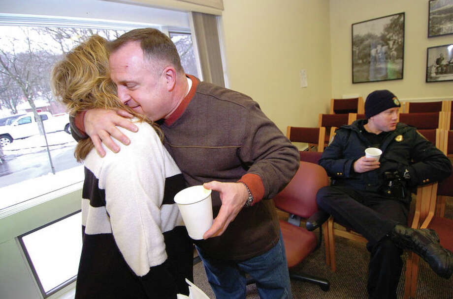 Hour Photo Alex von Kleydorff; Patrolman Diane MacLean gives a hug to Lt. Stephen Bartek III who is retiring after 31 years on the Wilton Police force. He is joined by friends from all town departments for coffee and cake at Town hall on Wednesday to wish him well / 2013 The Hour Newspapers