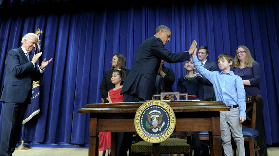 President Barack Obama, accompanied by Vice President Joe Biden, left, gets a high-five from eight-year-old letter writer Grant Fritz during a news conference on proposals to reduce gun violence, Wednesday, Jan. 16, 2013, in the South Court Auditorium at the White House in Washington. Obama and Biden were joined by law enforcement officials, lawmakers and children who wrote the president about gun violence following the shooting at an elementary school in Newtown, Conn., last month. (AP Photo/Susan Walsh) / AP