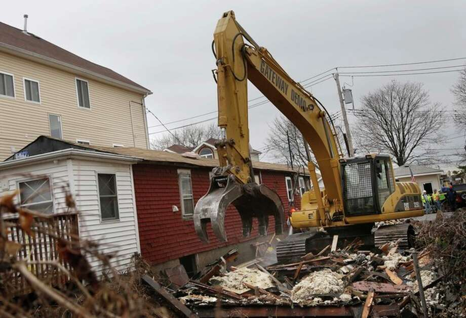 A home that was severely damaged by Superstorm Sandy is demolished in the Staten Island borough of New York, Monday, Jan. 14, 2013. Several Staten Island homes damaged beyond repair by Superstorm Sandy are being demolished. The first city-facilitated demolitions started Monday. (AP Photo/Seth Wenig) / AP