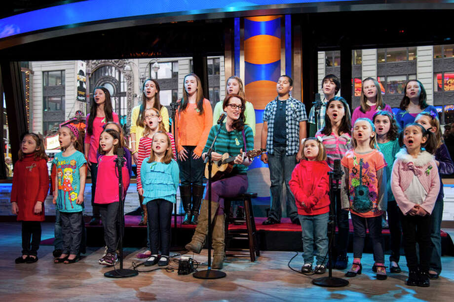 """Ingrid Michaelson accompanied by children from Newtown, Conn. and Sandy Hook Elementary school perform """"Somewhere Over the Rainbow"""" on ABC's """"Good Morning America"""" on Tuesday, Jan. 15, 2013 in New York. The Children who survived last month's shooting rampage, recorded a version of """"Over the Rainbow"""" to raise money for charity. They recorded the song at the home of two former members of the Talking Heads rock band. It went on sale Tuesday on Amazon and iTunes, with proceeds benefiting a local United Way and the Newtown Youth Academy. (Photo by Charles Sykes/Invision/AP) / Invision"""