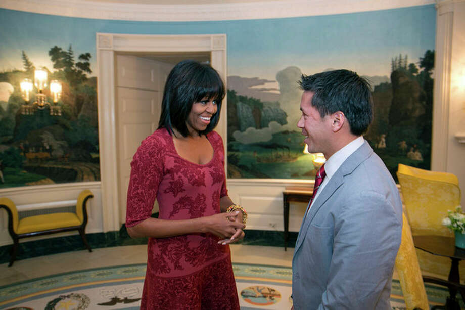 In this image released by the White House, first lady Michelle Obama greets David Hall, one of eight citizen co-chairs for the Inauguration, in the Diplomatic Reception Room of the White House in Washington, Thursday, Jan. 17, 2013. The photo is showing something different about Obama - bangs in her hair. (AP Photo/The White House, Lawrence Jackson) / The White House