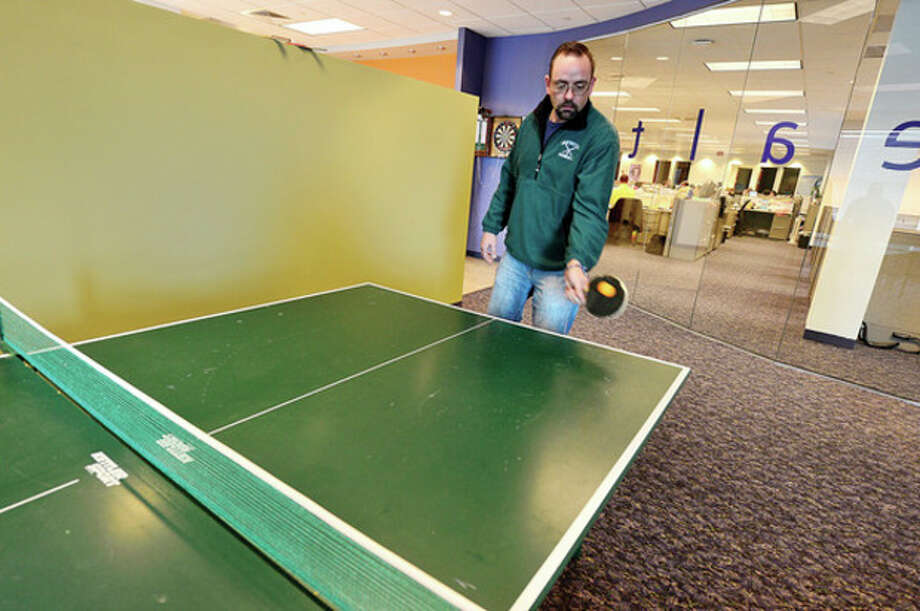 Comphealth employee John Pinto plays ping pong in the company's break room. Comphealth was named third-best company to work for by Fortune magazine.Hour photo / Erik Trautmann / (C)2012, The Hour Newspapers, all rights reserved