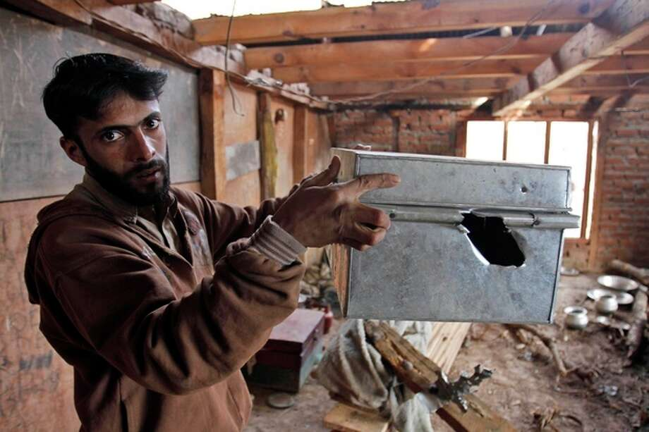 "Kashmiri villager Rafiq Ahamad displays a box allegedly damaged by firing from the Pakistan side of the border, inside his home near the Line of Control, the line that divides Kashmir between India and Pakistan, in Churunda village, about 150 Kilometers (94 miles) northwest of Srinagar, India, Tuesday, Jan. 15, 2013. India's relations with archrival Pakistan ""cannot be business as usual"" in the wake of a spate of attacks in Kashmir, Prime Minister Manmohan Singh said Tuesday in a statement that threatens to ratchet up tensions in the wake of the Himalayan violence. A series of tit-for-tat attacks, including the beheading of an Indian soldier, across the LOC that divides the Himalayan region has killed two Pakistani and two Indian soldiers over the past 10 days. (AP Photo/Mukhtar Khan) / AP"