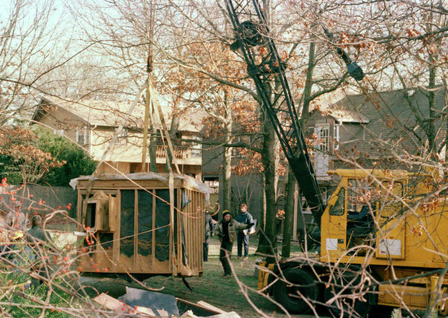 "FILE - In this Jan. 18, 1993 file photo, a crane raises a 6 foot by 9 foot bunker out of the earth from the property of John Esposito in Bay Shore, N.Y. Esposito kept 10-year-old Katie Beers imprisoned for 17 days in the cement and wood bunker, which contains a trap door. On the 20th anniversary of her ordeal, Beers has co-written a book with a television reporter who covered her kidnapping. ""Buried Memories: Katie Beers' Story"" (Title Town Publishing) has a happy ending. (AP Photo/Michael Alexander, File) / AP"