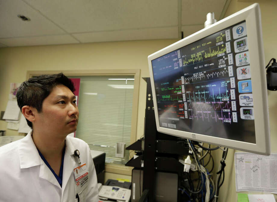 In this Monday, Jan. 14, 2013 photo, Dr. Steve Sun looks over a heart monitor display in the emergency room at St. Mary's Medical Center in San Francisco. A new government report shows the number of people seeking emergency treatment after consuming energy drinks has doubled nationwide over the last four years, the same period in which the supercharged industry has surged in popularity in convenience stores, bars and on college campuses. Sun said he had seen an increase in energy-drink related cases at the Catholic hospital where he works on the edge of San Francisco's Golden Gate Park. (AP Photo/Eric Risberg) / AP