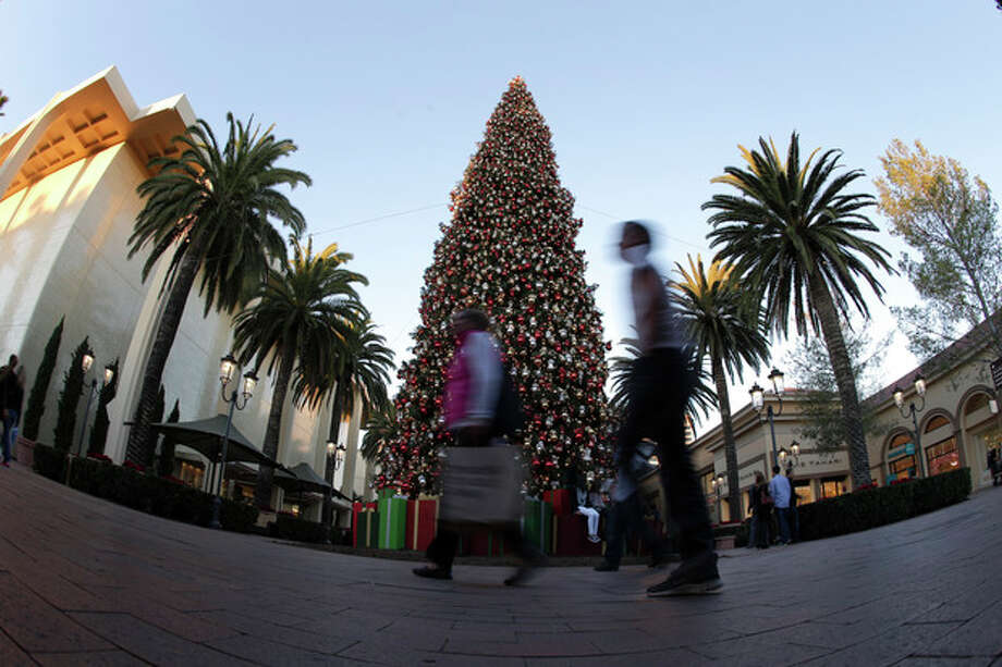 In this Thursday, Dec. 20, 2012, photo, holiday shoppers walk past a large Christmas tree at Fashion Island shopping center in Newport Beach, Calif. U.S. consumers increased their spending at retail businesses in December, buying more autos, furniture and clothing. (AP Photo/Chris Carlson) / AP