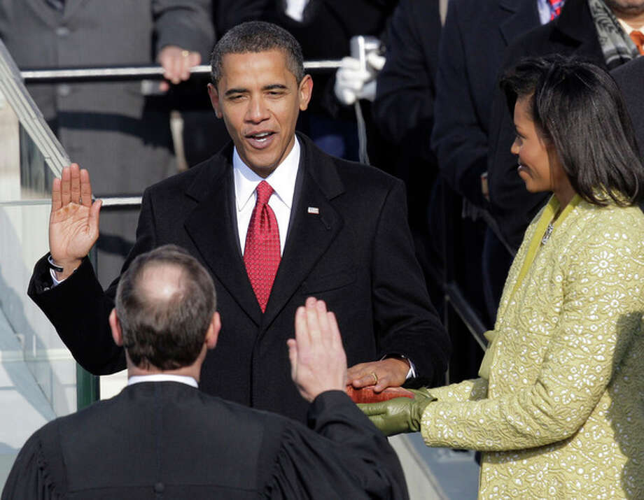 FILE - Barack Obama, left, joined by his wife Michelle, takes the oath of office from Chief Justice John Roberts to become the 44th president of the United States at the U.S. Capitol in Washington, D.C., in this Jan. 20, 2009 file photo. Obama is putting a symbolic twist on a time-honored tradition, taking the oath of office for his second term with his hand placed not on a single Bible, but two, one owned by Martin Luther King Jr. and one by Abraham Lincoln. (AP Photo/Jae C. Hong, File) / AP