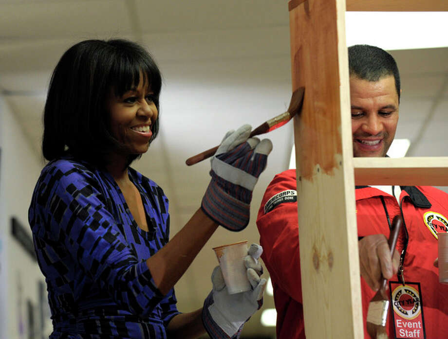ADD NAMES - First lady Michelle Obama, accompanied by Jeff Franco, executive director of City Year, stains a bookshelf at Burrville Elementary School in Washington, Saturday, Jan. 19, 2013, as the first family participated in a community service project for the National Day of Service, part of the 57th Presidential Inauguration. (AP Photo/Susan Walsh) / AP
