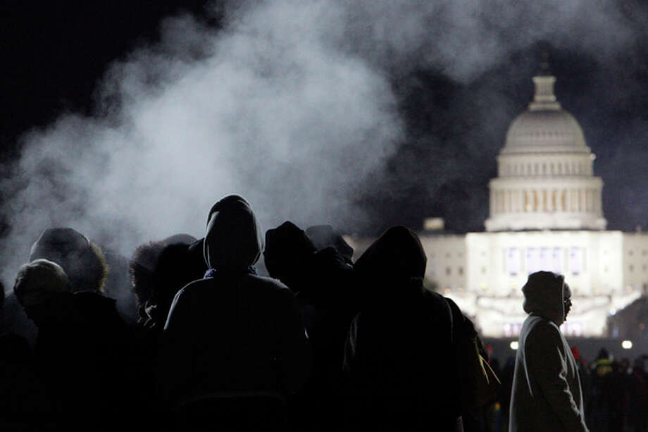 FILE - This Jan. 20, 2009 file photo shows people keeping warm near a steam vent on the National Mall in Washington prior to the start of then-President-elect Barack Obama's inauguration. It will be the first up or down fact check of a Barack Obama campaign pledge for his second term: Promised warmer Inauguration Day weather. Will he _ or Mother Nature _ deliver? It's looking like an uncomfortably close call _ the emphasis on the word uncomfortable for people who will be outside on what's predicted to be a downright chilly day. (AP Photo/Matt Rourke, File) / AP