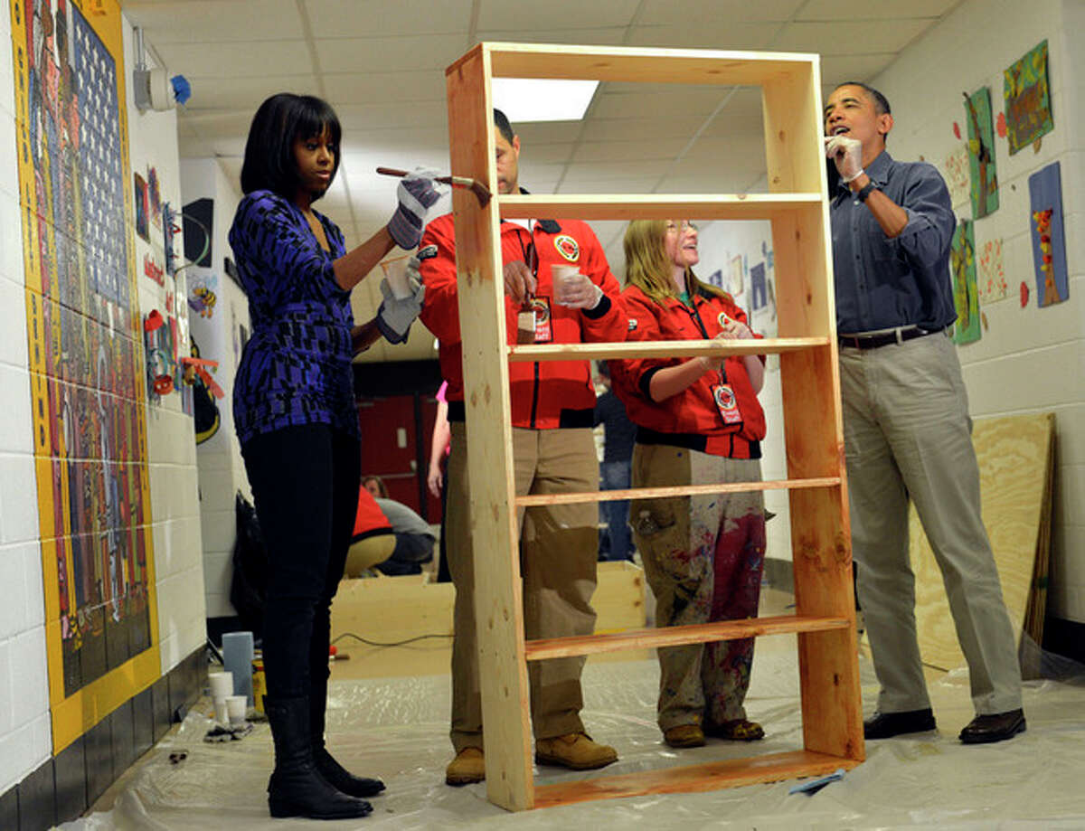 President Barack Obama, right, first lady Michelle Obama, left, City Year Executive Director Jeff Franco, City Year and City Year employee Sheri Fisher, second from right, stain a bookshelf at Burrville Elementary School in Washington, Saturday, Jan. 19, 2013, as the first family participated in a community service project for the National Day of Service as part of the 57th Presidential Inauguration. (AP Photo/Susan Walsh)