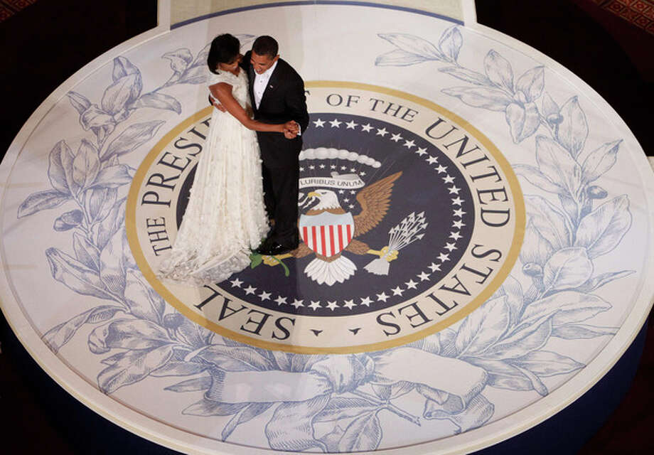 FILE - In this Jan. 20, 2009, file photo, President Barack Obama and first lady Michelle Obama dance at the Commander in Chief Inaugural Ball at the National Building Museum in Washington. Obama's second inauguration is shaping up as a high-energy celebration smaller than his first milestone swearing-in, yet still designed to mark his unprecedented role in American history with plenty of eye-catching glamour. A long list of celebrity performers will give the once-every-four years right of democratic passage the air of a star-studded concert, from the bunting-draped Capitol's west front of the Capitol, where Obama takes the oath Jan. 21, to the Washington Convention Center, which is expected to be packed with 40,000 ball-goers that evening. (AP Photo/Charles Dharapak, File) / AP
