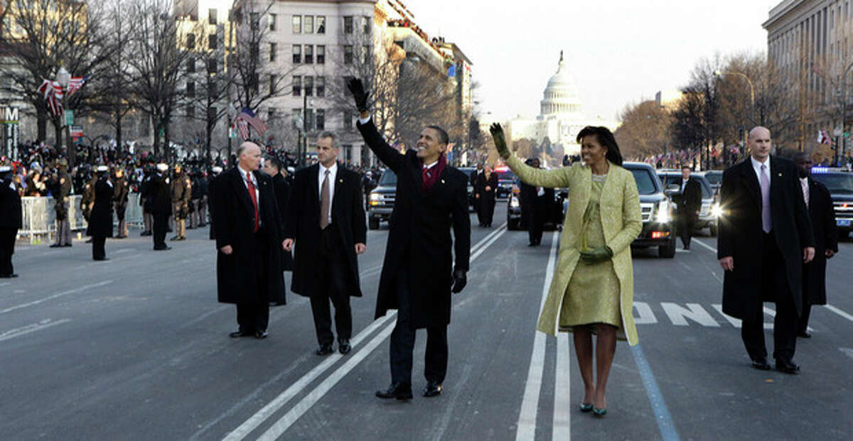 FILE - This Jan. 20, 2009 file-pool, photo shows President Barack Obama and first lady Michelle Obama waving as they walk down Pennsylvania Avenue en route to the White House from the Capitol in Washington. At some point on Inauguration Day, if all goes expected, the president?•s limousine will slow to a stop on its journey down Pennsylvania Avenue from the Capitol to the White House. A Secret Service agent will open the rear passenger door, and the newly sworn-in president will emerge from his car for a several-minute stroll. The crowd will cheer. The president will wave. In that moment, Pennsylvania Avenue is America?•s red carpet. And the president is the only celebrity on it. The victory walk has become an iconic inaugural moment, one expected by the public and the press. And though the tradition dates only to President Jimmy Carter, it has already developed an air of inevitability and predictable patterns. (AP Photo/Doug Mills, File, Pool)