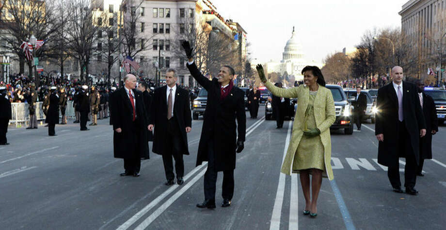 FILE - This Jan. 20, 2009 file-pool, photo shows President Barack Obama and first lady Michelle Obama waving as they walk down Pennsylvania Avenue en route to the White House from the Capitol in Washington. At some point on Inauguration Day, if all goes expected, the presidentÕs limousine will slow to a stop on its journey down Pennsylvania Avenue from the Capitol to the White House. A Secret Service agent will open the rear passenger door, and the newly sworn-in president will emerge from his car for a several-minute stroll. The crowd will cheer. The president will wave. In that moment, Pennsylvania Avenue is AmericaÕs red carpet. And the president is the only celebrity on it. The victory walk has become an iconic inaugural moment, one expected by the public and the press. And though the tradition dates only to President Jimmy Carter, it has already developed an air of inevitability and predictable patterns. (AP Photo/Doug Mills, File, Pool) / AP