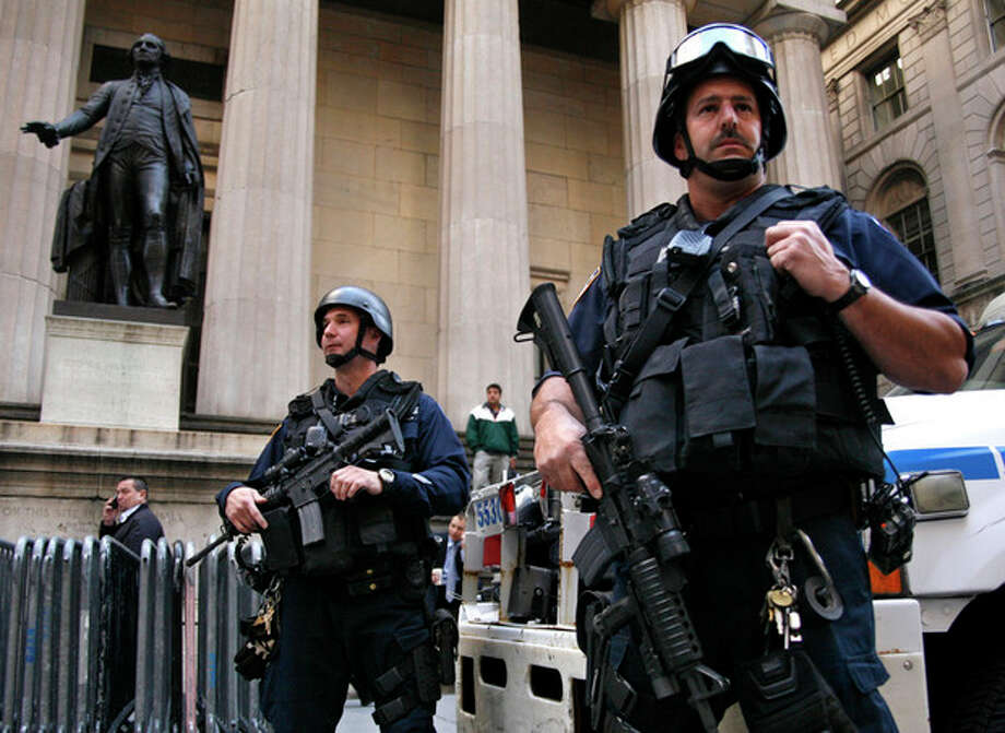 FILE - In this Friday, May 7, 2010 file photo, armed officers from the New York Police Department's Emergency Service Unit make a routine appearance in the financial district in New York. In the wake of Saturday night's failed car bombing in Times Square, jittery authorities are pouncing on anything suspicious and overwrought headlines are keeping the city on edge. A statue of George Washington, left, stands in front of Federal Hall. (AP Photo/Peter Morgan) / AP