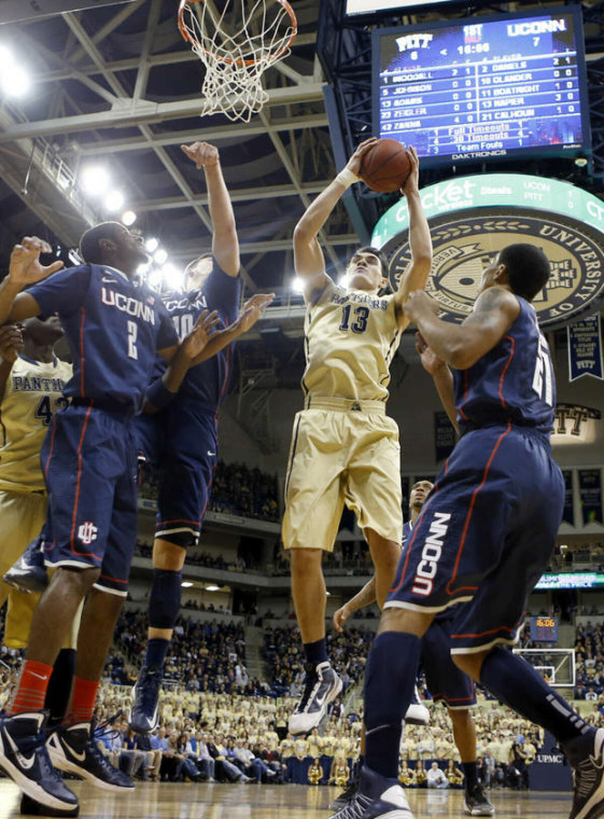 Pittsburgh's Steven Adams (13) goes up for a shot between Connecticut's DeAndre Daniels (2) and Omar Calhoun (21) during the first half of an NCAA college basketball game, Saturday, Jan. 19, 2013, in Pittsburgh. (AP Photo/Keith Srakocic)