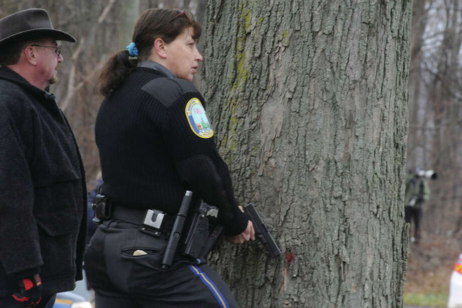 Police wait outside Saint Rose of Lima church in Newtown Sunday when a threat was called in during the service. hour photo/Matthew Vinci / (C)2011 {your name}, all rights reserved