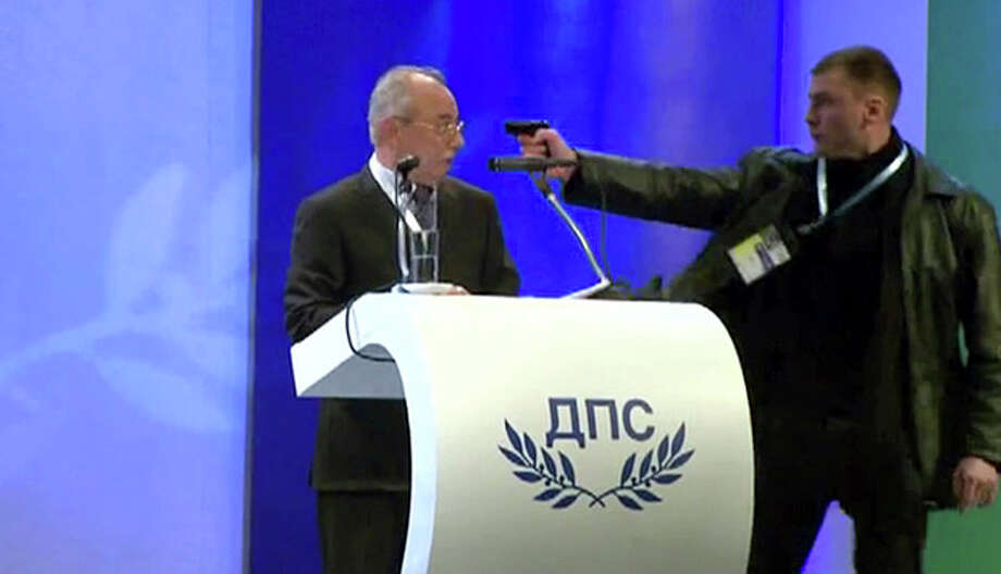 Image grab from video shows a man identified as Oktai Enimehmedov, 25, as he points a weapon at Ahmed Dogan, left, leader of the Movement for Rights and Freedoms, during his speech at his party's congress in Sofia, on Saturday Jan. 19, 2013. Dogan struck the man before other delegates wrestled the assailant to the ground, and no shots were fired. Police took the man away.(AP Photo/ BTVnews) / BTV NEWS