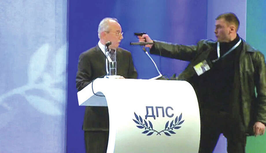 AP photo / BTVnewsImage grab from video shows a man identified as Oktai Enimehmedov, 25, as he points a weapon at Ahmed Dogan, left, leader of the Movement for Rights and Freedoms, during his speech at his party's congress in Sofia, on Saturday. / BTV NEWS