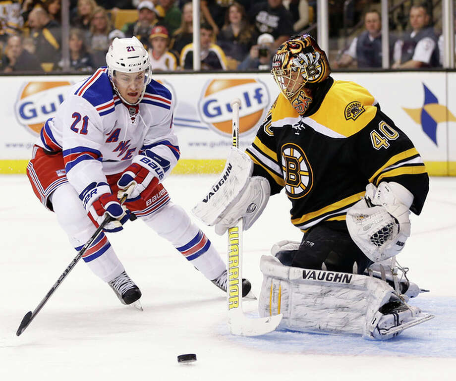 New York Rangers' Derek Stepan (21) skates for the rebound off Boston Bruins goalie Tuukka Rask (40), of Finland, during the first period of an NHL hockey game in Boston, Saturday, Jan. 19, 2013. (AP Photo/Michael Dwyer) / AP