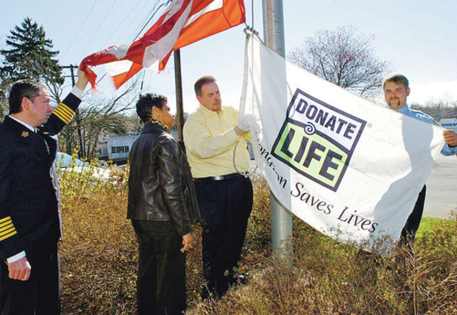 Hour photo / Erik TrautmannAbove, Westport Fire Chief Andrew DiPietro, Donate Life volunteers Dara Brooks and Bruce Adams and Westport firefighter Joe Arnson raise the Donate Life flag following a press conference on the importance of organ donation Wednesday at the Westport Fire Department. Below, Donate Life volunteer Dara Brooks recalls how organ donation saved her son's life / (C)2011, The Hour Newspapers, all rights reserved
