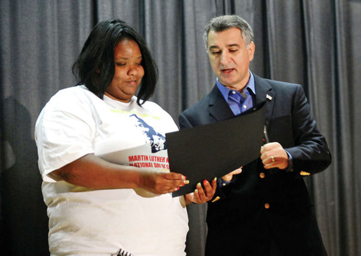 Hour photo / Erik Trautmann Darren Dix, left, receives special recognition from State Sen.Carlo Leone, D-Stamford, Senate chairman of the General Assembly's Veterans' Affairs Committee, during the Trailblazer Academy's MLK Day of Service Saturday.