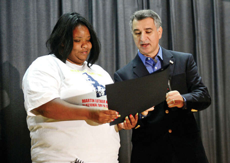 Hour photo / Erik TrautmannDarren Dix, left, receives special recognition from State Sen.Carlo Leone, D-Stamford, Senate chairman of the General Assembly's Veterans' Affairs Committee, during the Trailblazer Academy's MLK Day of Service Saturday. / (C)2012, The Hour Newspapers, all rights reserved